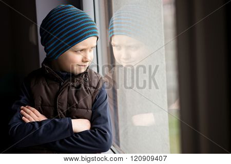 Confident 7 year old boy looks out the window
