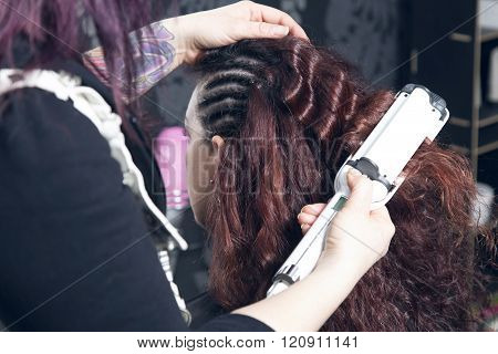 Hairdresser Ironing One Customer's Curled Hair.