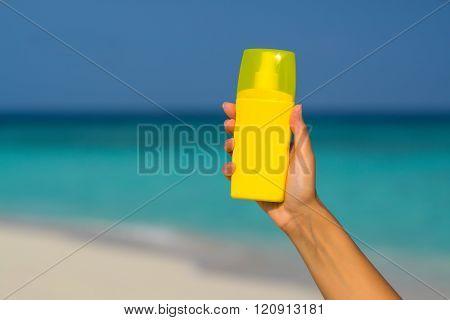 Sunscreen Cream Bottle In Hand On Tropical Beach