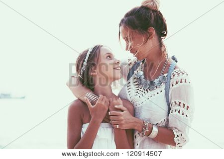 Tween daughter hugging with her mom, boho oriental style