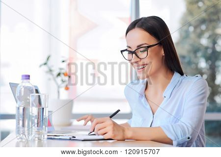 Pleasant business woman sitting at the table