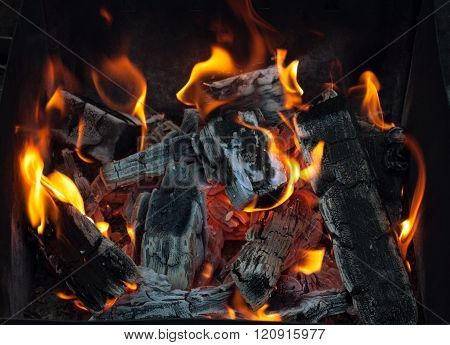 Closeup of charcoal burning under a barbecue grill. 