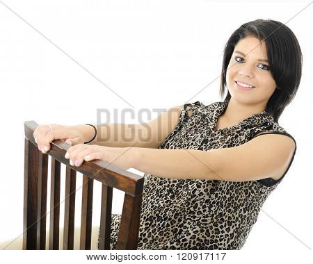 Portrait of a happy teen girl sitting backwards on a chair and leaning back.  On a white background.