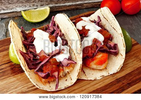 Spicy fish tacos with cabbage slaw, salsa and sour cream