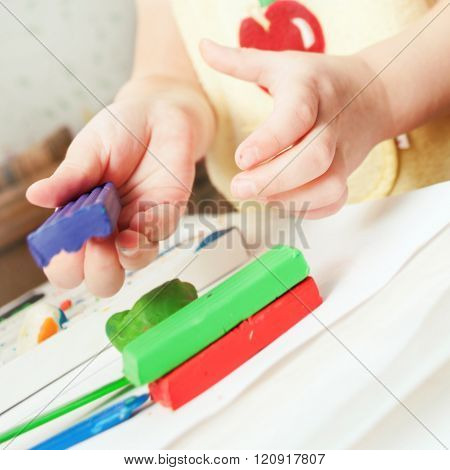 Child moulds from modeling clay on table. hands with modeling clay. Little girl is learning to use colorful play dough