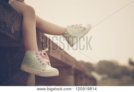 a girl sitting on a bridge with her feet pointing down to the river in vintage tone