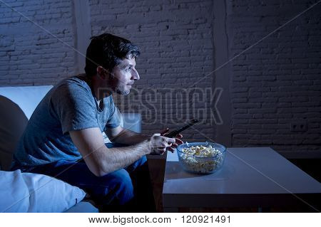 young happy television addict man sitting on home sofa watching TV eating popcorn using remote control enjoying movie sitcom or live sport at night