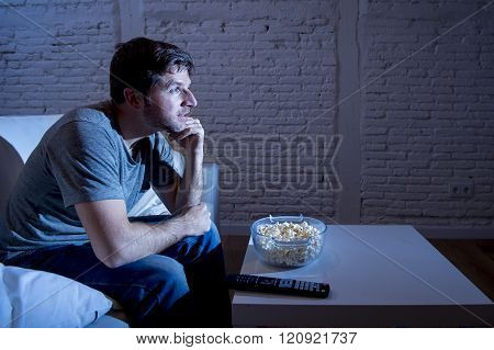 young happy television addict man sitting on home sofa watching TV and eating popcorn looking mesmerized smiling while enjoying movie sitcom or live sport at night