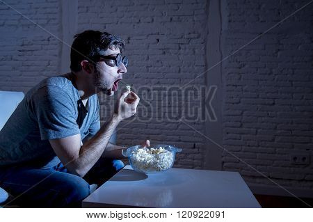 young television addict man sitting on home sofa watching TV and eating popcorn wearing funny nerd and geek glasses looking mesmerized enjoying movie sitcom or live sport at night