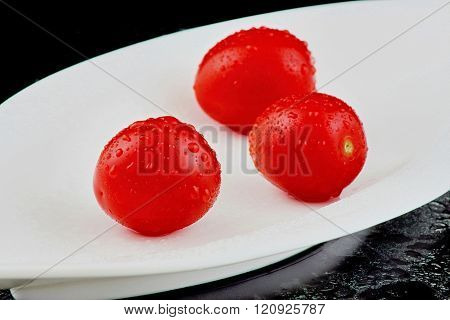 Three tomatoes in a white porcelain dish