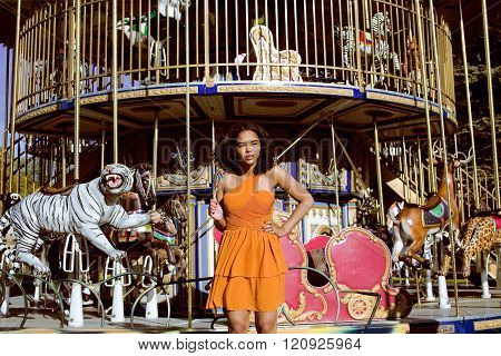 cool real teenage girl with candy near carousels at amusement park walking, having fun