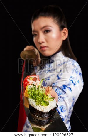 Young asian beauty is holding sushi on katana
