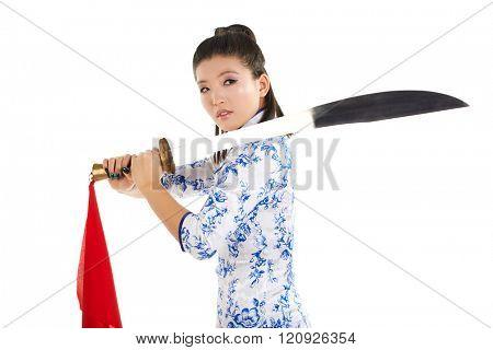 young beautiful Japanese woman in kimono looking aggressively at camera and holding katana sword