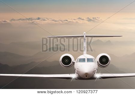 Travel concept. Airplane fly over clouds and Alps mountain on sunset. Front view of a big passenger