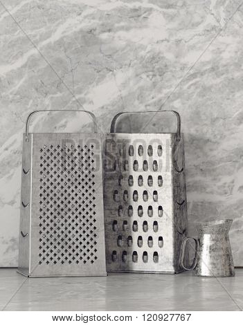 Two old upright stainless steel cheese graters on a kitchen counter with a shaker in front f a stone textured grey wall with copy space. 3d Rendering.
