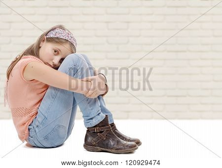 preteen girl sad  is sitting on the floor