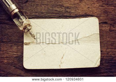 Obsolete Glass Syringe On Old Wooden Table