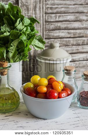 Fresh Tomatoes In A Ceramic Bowl, Green Garden Herb, Olive Oil And Spices On A Light Rustic Wood Bac