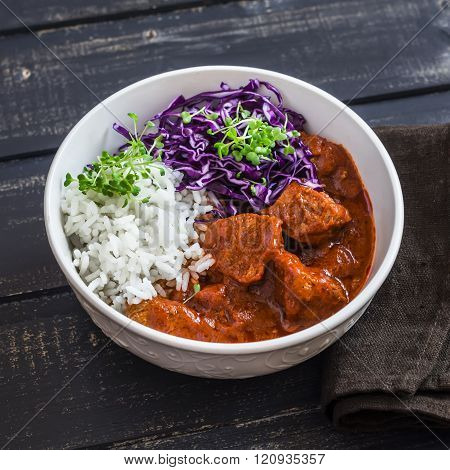 Stewed Meat In Tomato Sauce, Rice, Red Cabbage  On A Dark Wooden Table. Delicious Healthy Lunch
