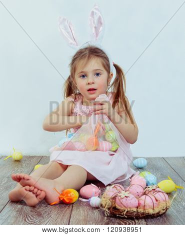 Preschool kid with Easter bunny ears on  playing with colorful eggs