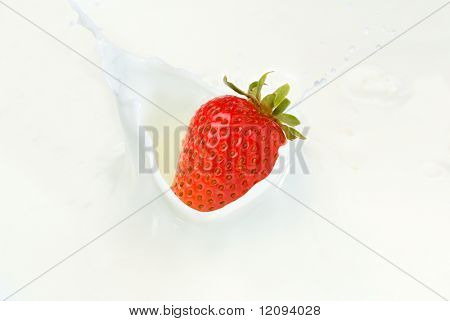Extreme close-up image of a strawberry splashing into milk