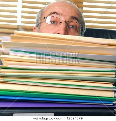 Man with a work overload in front of him