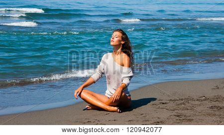 young woman enjoy in sunbath at sandy beach by the sea full body shot