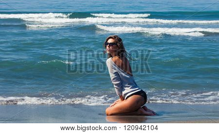 fashion summer girl on sandy sea beach in bikini and tunic enjoy in water and sun side view full body shot