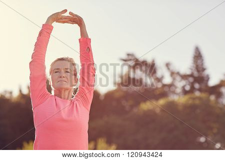 Sporty senior woman doing exercise warm-up stretches outdoors