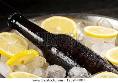 ale bottle in an iron bucket with ice and lemon