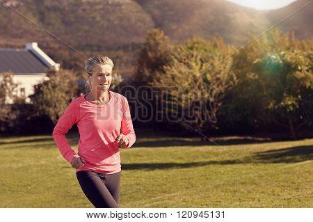 Athletic senior woman jogging outdoors on sunlit morning in natu