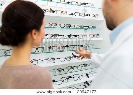 health care, people, eyesight and vision concept - close up of optician showing glasses to woman at optics store