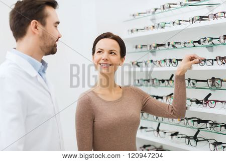 health care, people, eyesight and vision concept - happy woman choosing glasses and optician at optics store