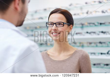 health care, people, eyesight and vision concept - happy woman in glasses looking and talking to optician at optics store
