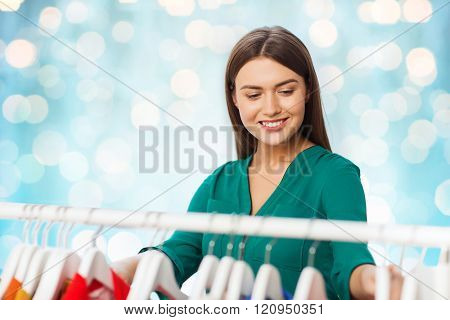 clothing, fashion, style and people concept - happy woman choosing clothes at wardrobe over blue holidays lights background
