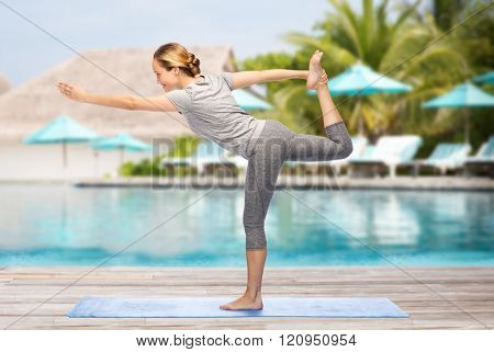 fitness, sport, people and healthy lifestyle concept - woman making yoga in lord of the dance pose on mat over beach and swimming pool background
