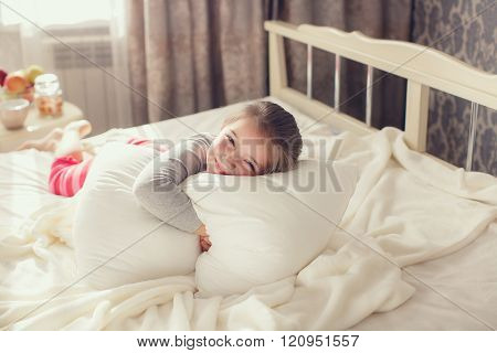 Morning portrait of a little girl waking up,embracing the pillow