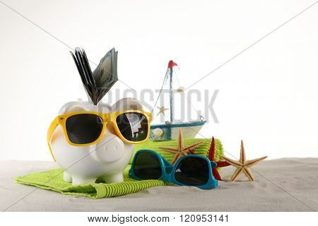 Piggy bank with inserted dollar banknotes, towel and sunglasses on a sand, isolated on white. Holiday money concept