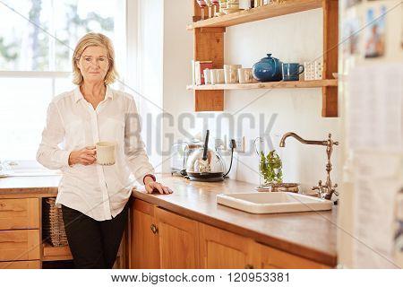 Worried looking senior woman standing in her kitchen