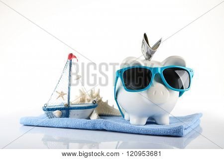 Piggy bank with inserted dollar banknote, towel and sunglasses, isolated on white. Holiday money concept