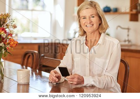 Senior woman smiling while holding a phone in her kitchen