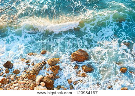 Waves on a rocky beach at sunset. Aerial view