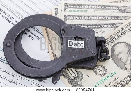 Handcuffs And Money With Sign – Debt On Tax Form Background