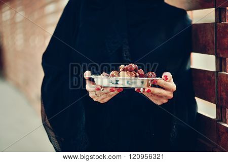 Emirati arab woman holding dates plate
