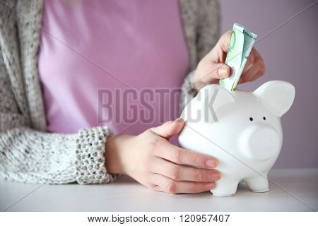 Woman putting dollar banknote into white piggy bank at the table