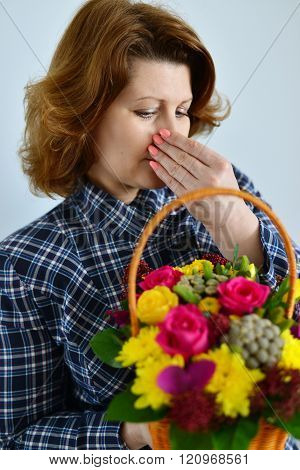 woman with allergic rhinitis is holding a bouquet of a flowers