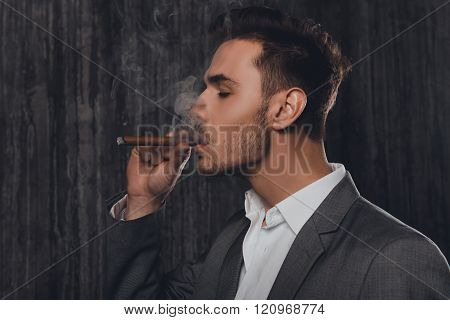 Side View Of A Cheeky Man In Suit On The Grey Background Smoking A Cigar