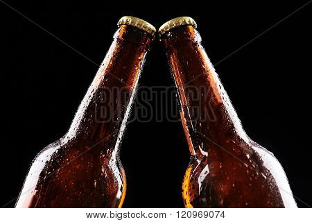 Two glass bottles of beer on black background