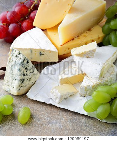 Various Types Of Fresh Cheese With Grapes On Slate