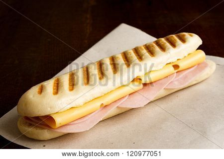 Cheese And Ham Toasted Panini. On Brown Paper And Wood.
